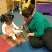 UDM student Chantel Ellis reads an RX for Reading book with a Peggy's Place preschooler.
