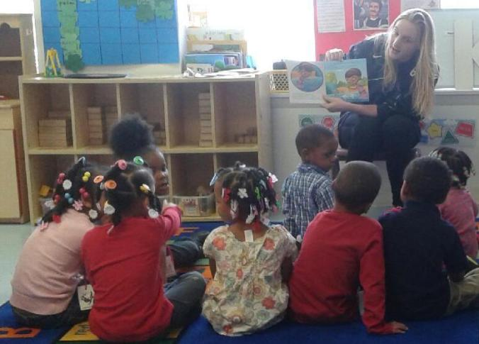 UDM Business major Anna Mindling reads Doc McStuffins with the kids at Emmanuel