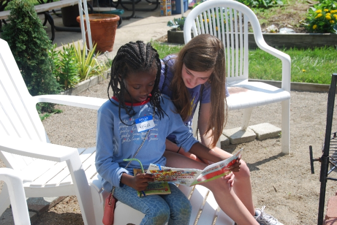 A camper and counselor read at the Minock Park Summer in the City Camp.