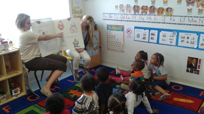UDM undergraduates Emily Auten and Alyssa Burgess read with the kids at Emmanuel Head Start.
