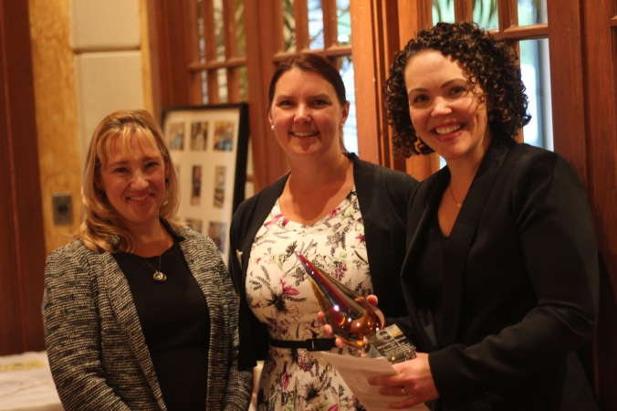 Mary-Catherine Harrison (right) after being presented the Bookwoman Award by Shannon Jones Janeczek (left), President of the WNBA Detroit Chapter and Tanya Davidson (middle), WNBA Detroit Award Chair.