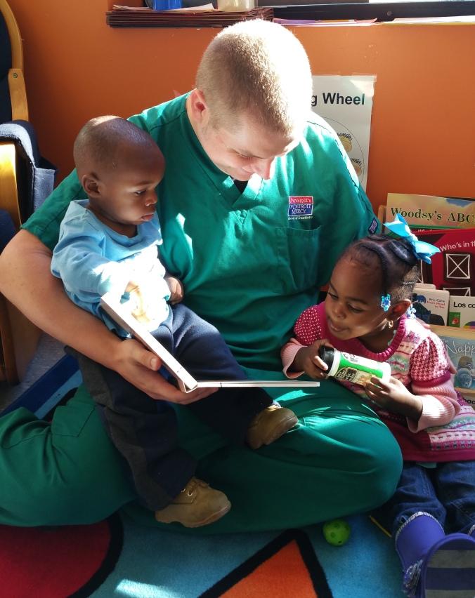 UDM senior dental student David Posthumus reads with Julius and Ahlinius Grant.